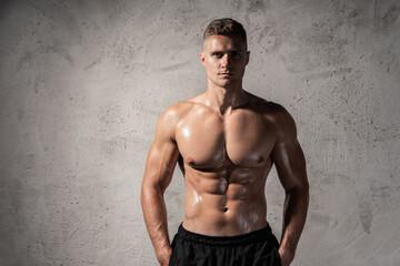 Sweaty young bodybuilder with a muscular body - fototapety na wymiar