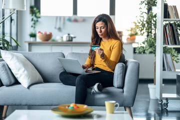 Fototapeta Beautiful young woman paying something online with her credit card in laptop while sitting on couch at home. obraz