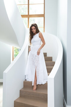 Gorgeous woman wearing beautiful white dress on a staircase inside her house