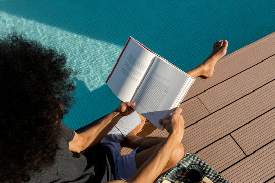 relaxed man reading  by the pool