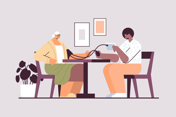 nurse or volunteer checking blood pressure to elderly woman home care services healthcare and social support - fototapety na wymiar