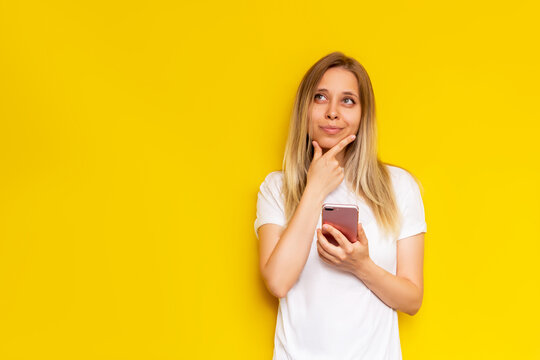 A young caucasian pretty thoughtful blonde woman in a white t-shirt with mobile phone in her hand thinks looking away at empty copy space for text or design isolated on bright color