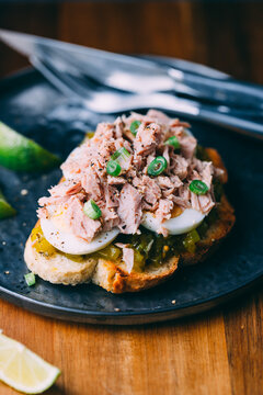 Open sandwich with canned tuna, egg and pickled cucumber dressing served with lime.