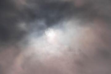 Światło słoneczne przebijające się przez warstwę ciemnych chmur.