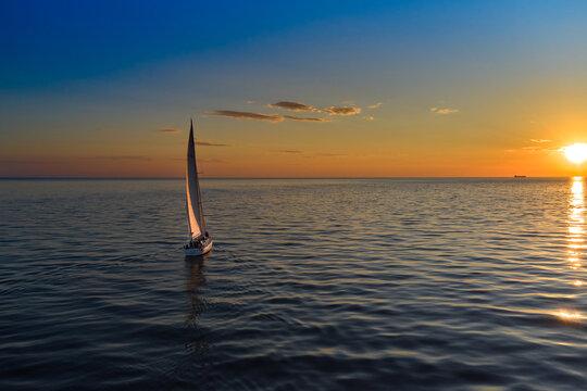 Riga, Latvia 12-06-2021 Yacht sailing against sunset. Holiday lifestyle landscape with skyline sailboat. Yachting tourism - maritime evening walk. Romantic trip on luxury yacht during the sea sunset.