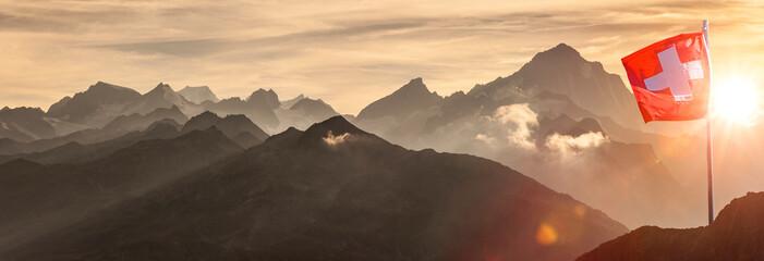 Fototapeta Schweizer Flagge vor Alpenpanorama im Hochgebirge obraz