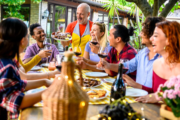 Group of happy friends drinking red wine in a garden while waiter is serving them grilled meat - Happy friends eating bbq food at restaurant - Life style concept about friendship and happiness