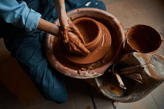 Beautiful elegant ceramicist hands shaping ceramic bowl on pottery wheel in workshop