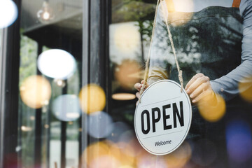 Fototapeta hand of asain staff woman wearing apron turning open sign board on glass door in modern cafe coffee shop, hotel service, cafe restaurant, retail store, small business owner, food and drink concept obraz