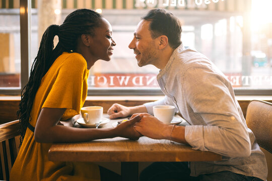 Happy diverse couple during date in cafe