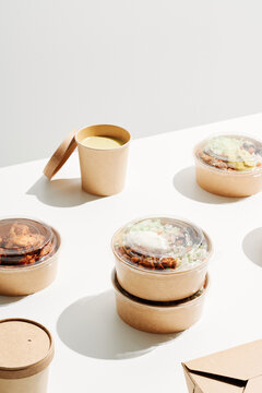 Carton bowls with delivered food on table