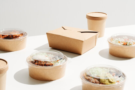 Variety of carton takeaway containers with food and drinks