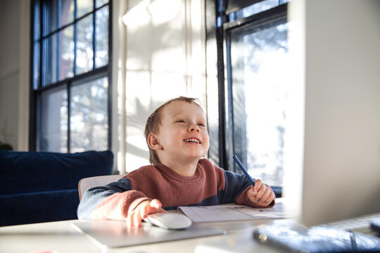 Little boy smiling while using desktop computer
