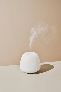 Modern essential oil diffuser on table