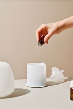 Anonymous person pouring essential oil into diffuser