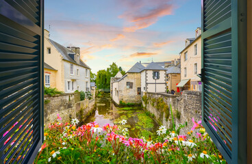 View through an open window with shutters above a small stream with medieval homes nearby, at sunset in the French Village of Bayeux, France, in the Normandy region.
