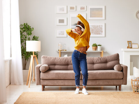Young playful african american woman in headphones jumping and dancing in living room at home