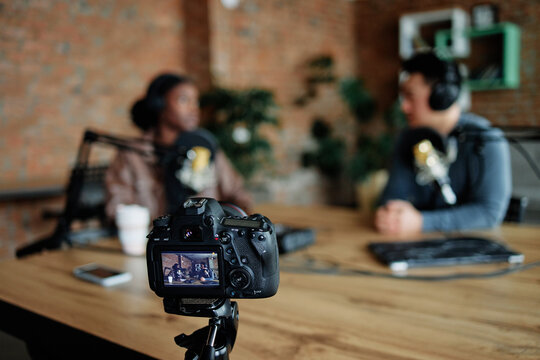 Man and woman shooting their podcast on camera for audience
