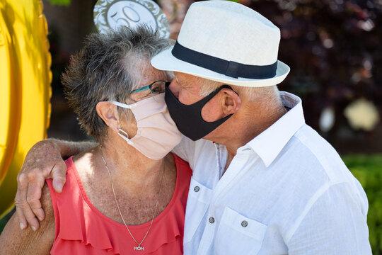 Senior Citizen Couple Kissing In Masks at Golden 50th Wedding Anniversary