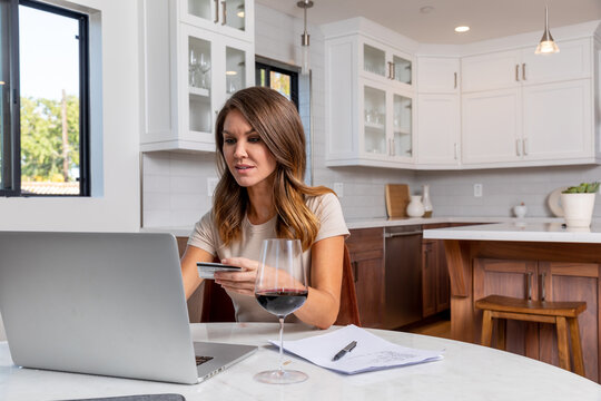 Woman Holds a Card and Types on a Computer