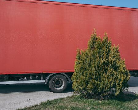 A bush against a red truck trailer