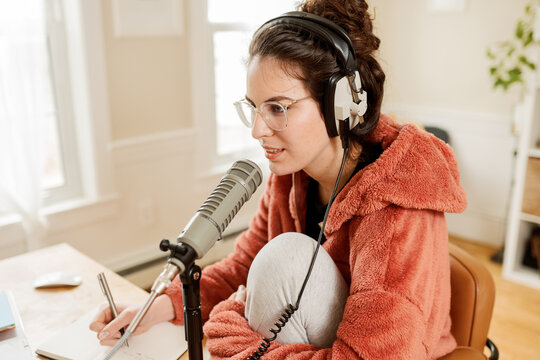 woman taking notes while doing a podcast