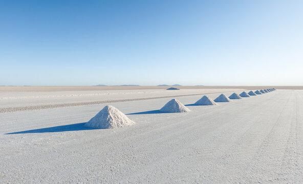 Salt mining in Colchani with salt pyramids ready for harvest, Uyuni salt flat (Salar de Uyuni), Bolivia, South America.