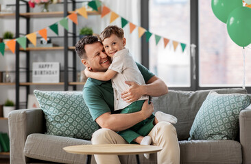 family, fatherhood and people concept - portrait of happy smiling father and little son hugging at...