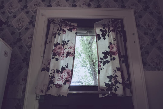 Flower-patterned wall and curtain with bright window in kitchen