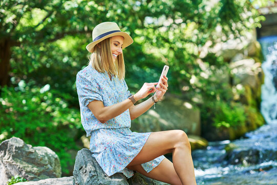 A nice girl sitting on a rock with smartphone