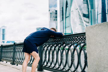Young tired fitness man runner relax and stretching after exercise run outdoors in city urban street. Healthy lifestyle and sport concept. Tired after workout