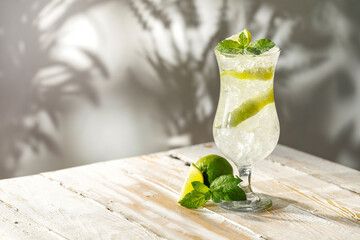 Mint lime on a wooden white table on a summer day and shadows of leaves on the wall