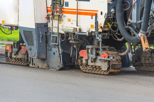 Support pillars of heavy industrial road machinery for repairing the road asphalt pavement.