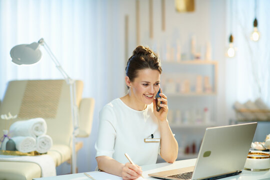 happy woman worker in beauty salon talking on phone