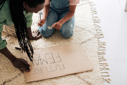 Anonymous girl and her father preparing a banner for feminist protests