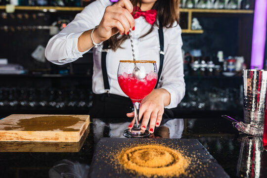 Anonymous stylish woman preparing alcoholic cocktail in modern bar