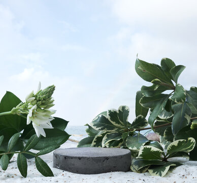 Natural stone and concrete podium on tropical beach with flowers. Empty showcase for packaging product presentation. Background for cosmetic products, scene with green leaves. Mock up pedestal.