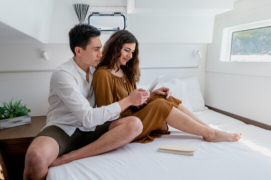 Couple using tablet in cabin of yacht