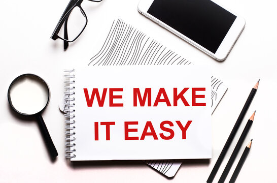 On a white background glasses, a magnifier, pencils, a smartphone and a notebook with the text WE MAKE IT EASY