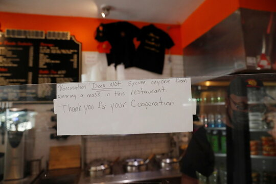 A sign urges clients to wear face masks at a restaurant in New York City