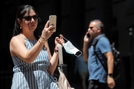 A tourist holds her mask while using her phone for a selfie on Wall Street outside of the NYSE in New York