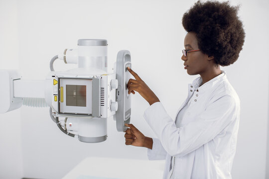 Close up portrait of young African American lady doctor working with modern X-ray machine for scanning human body. Roentgen of chest bone. Medical examination