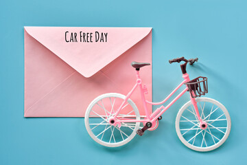Car free day September 22. Toy model town bike on mint blue background. Text on pink paper envelope. Flat lay, top view, minimal retro vintage concept design.