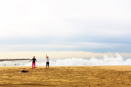 Two middle age women do yoga on a sandy beach by the stormy sea. Barcelona, Spain