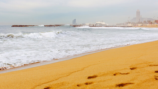 Sea view and city view from the coastal strip of the Mediterranean Sea with a sandy beach in the area of San Martí in Barcelona, Spain