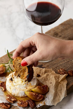 Baked brie with fresh figs and honey, served with glass of red wine