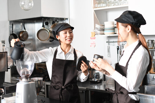 飲食店で働くエプロン姿の女性達
