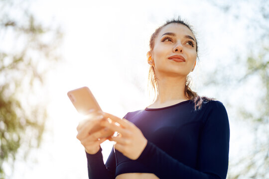 Young woman turns on music for running on her smartphone outdoors
