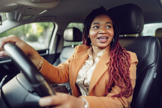 Portrait of positive african american lady inside the car