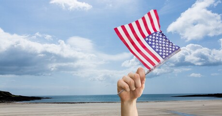 Samenstelling van man met wuivende Amerikaanse vlag tegen lucht en zee